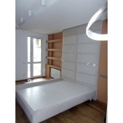 Bed with a wall panel